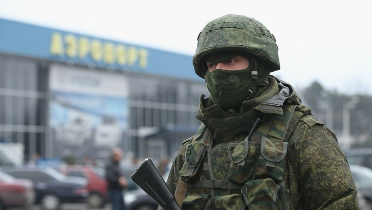Een soldaat patrouilleert voor het vliegveld van Simferopol op de Krim. Beeld getty
