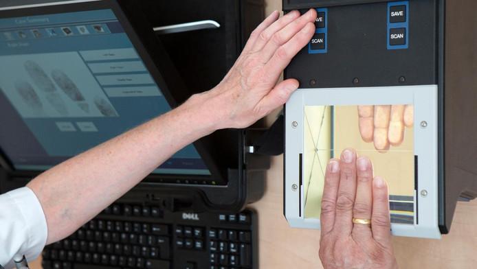 Verpleegkundige Leni van Doorn neemt een vingerafdruk af bij een patiënt