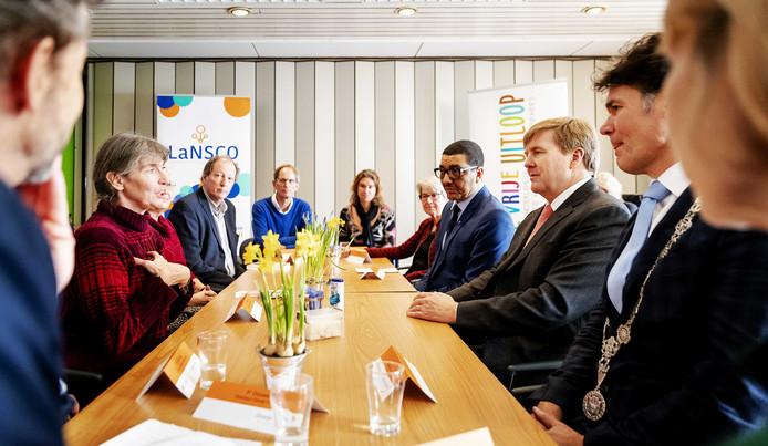 Koning Willem-Alexander in gesprek met initiatiefnemers van De Vrije Uitloop en vergelijkbare coöperaties. Aan het woord is links Erna Smeekens, oprichtster van het project in Breda. De koning wordt geflankeerd door Jörgen Raymann (bestuurslid Oranjefonds) en burgemeester Paul Depla.