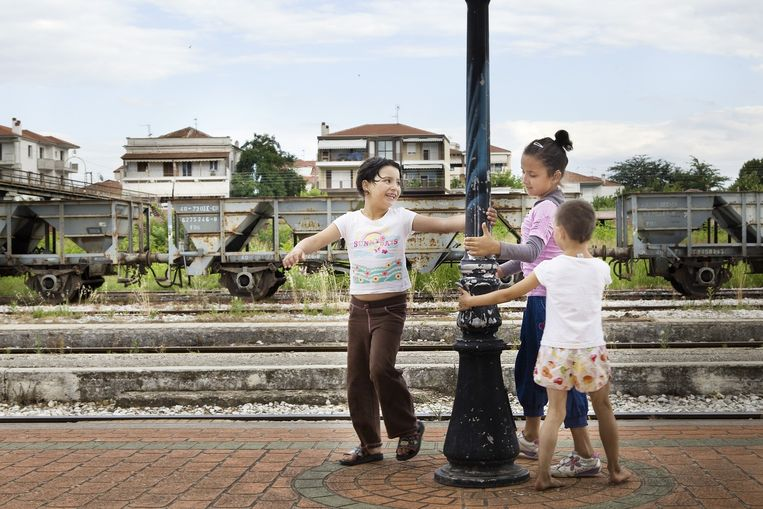Drie Bulgaarse zusjes spelen met de lantaarnpalen terwijl ze op de trein wachten. Beeld Io Cooman.
