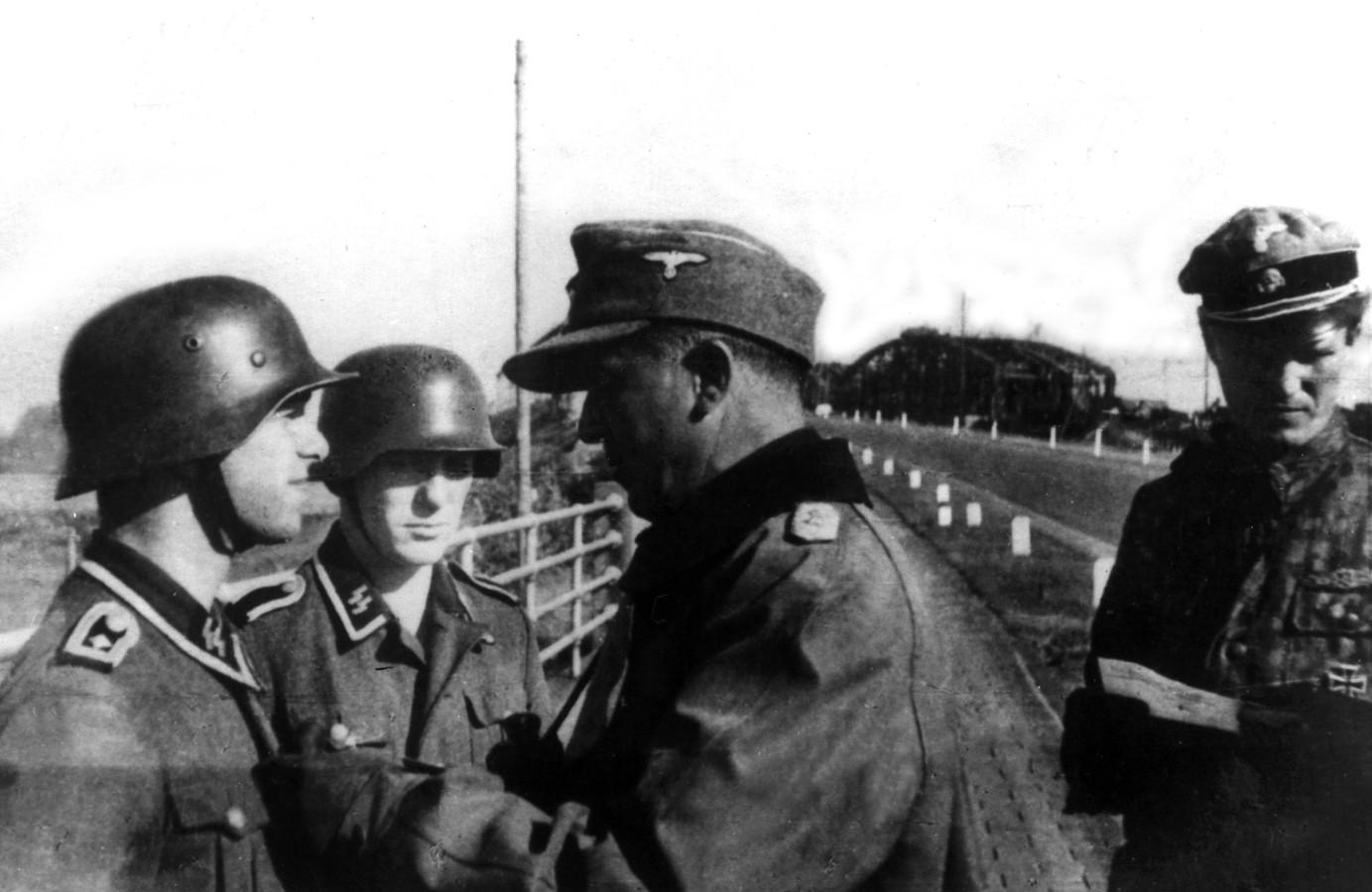 Michael Lippert, commandant van de Unterführerschule Arnheim, speldt twee SS'ers onderscheidingen op vlakbij de bruggen over de Waal bij Zaltbommel. Rechts Oskar Pahnke.