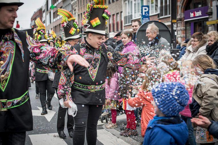 Enkele carnavalisten overladen de toeschouwers met confetti.