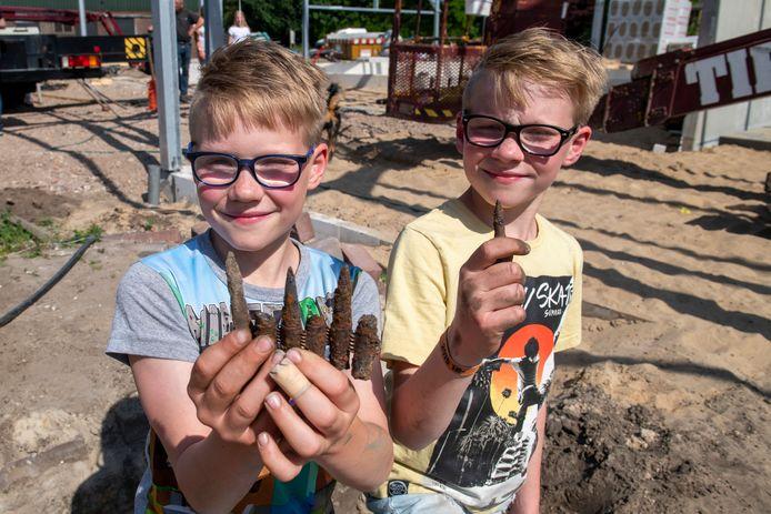 Jurre en Quinn met oude kogels in hun handen. De tweeling uit Hein vond ook een granaat die nog op scherp stond.