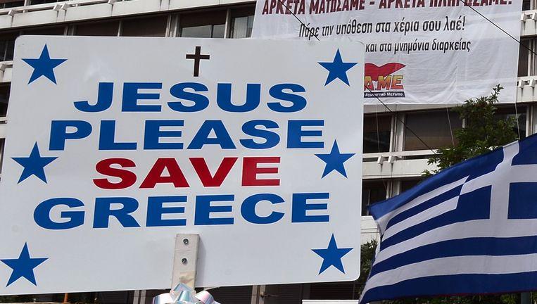 Een demonstrant houdt dit opmerkelijke plakkaat naar boven bij een betoging in Athene.