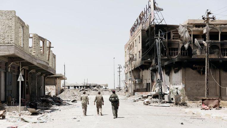 Iraakse militairen inspecteren Falluja. De Iraakse stad ligt vol mijnen. 'Liefst knippen we de draad door. We blazen de huizen niet graag op, straks moeten de bewoners weer terug.' Beeld Daniel Rosenthal / de Volkskrant