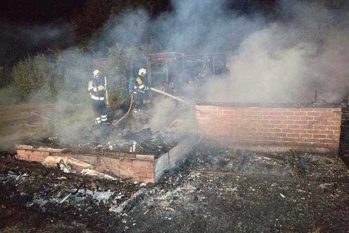 Brandweerlieden blussen de brand in de stacaravan