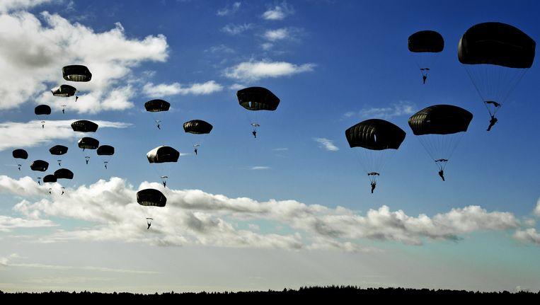 Zo'n duizend parachutisten springen boven de Ginkelse Heide met een parachute uit een vliegtuig. Met de sprong eren ze alle veteranen die in de Tweede Wereldoorlog deelnamen aan Operatie Market Garden. Beeld ANP