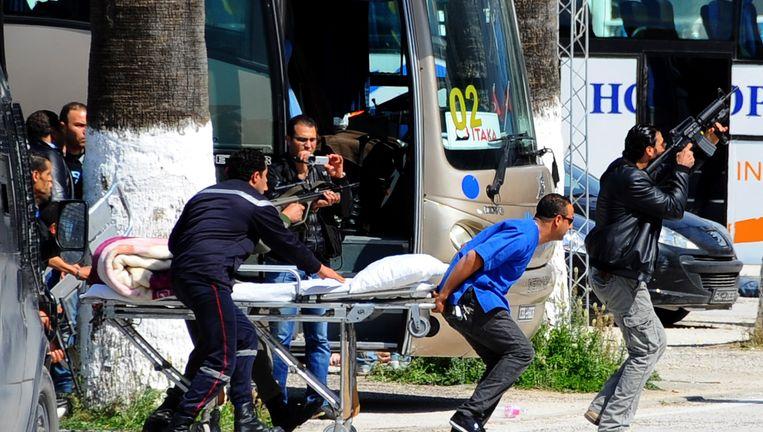 Politie en veiligheidspersoneel met een lege stretcher bij het Bardo museum Beeld ap