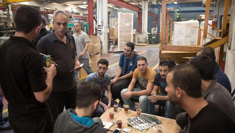 Palestijnse werknemers van een Israëlische plasticfabriek vlakbij de Israëlische nederzetting Ariel op de Westelijke Jordaanoever. Beeld afp