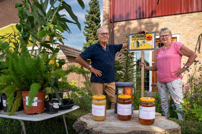 Wim en An Klerks bij hun buurtwinkeltje met planten en honing.