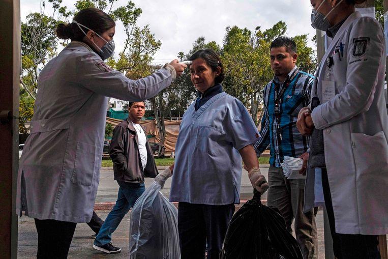 Een verpleegster neemt de temperatuur op van medewerkers bij de ingang van het ziekenhuis van Tijuana in Mexico.  Beeld AFP