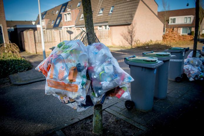 De containers en afvalzakken liggen buiten.