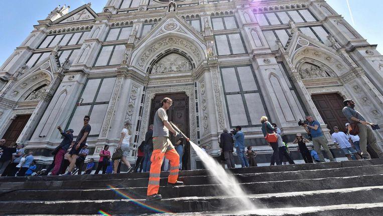 De trappen voor de Basilica di Santa Croce in Florence worden natgespoten zodat toeristen er niet blijven bivakkeren Beeld EPA