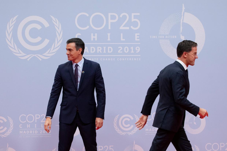 Mark Rutte loopt langs premier Pedro Sanchez van Spanje bij de opening van de klimaattop. Beeld Getty Images