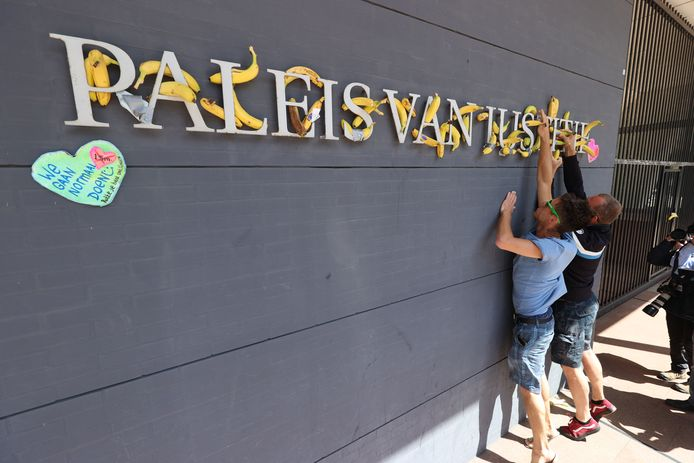 Actievoerders plakken bananen op de muur van de Haagse rechtbank.