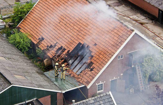 De brand in de schuur aan de Suetersweg in Bentelo. Er brand vooral hooi, waar de brandweer grote moeite mee heeft. Het hooi wordt de komende uren uit de schuren gehaald en apart afgeblust.