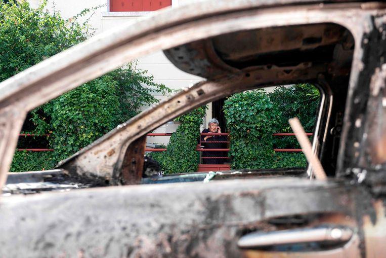 Een buurtbewoonster kijkt naar een uitgebrande wagen.