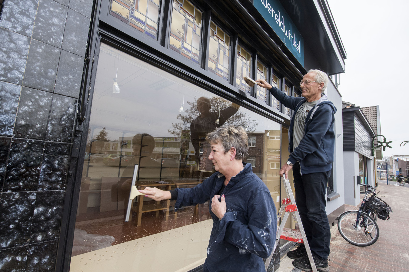 Ursula Drexhage en Bert Westhuis maken de oude Wereldwinkel schoon.  Het wordt straks de Weggeefwinkel.
