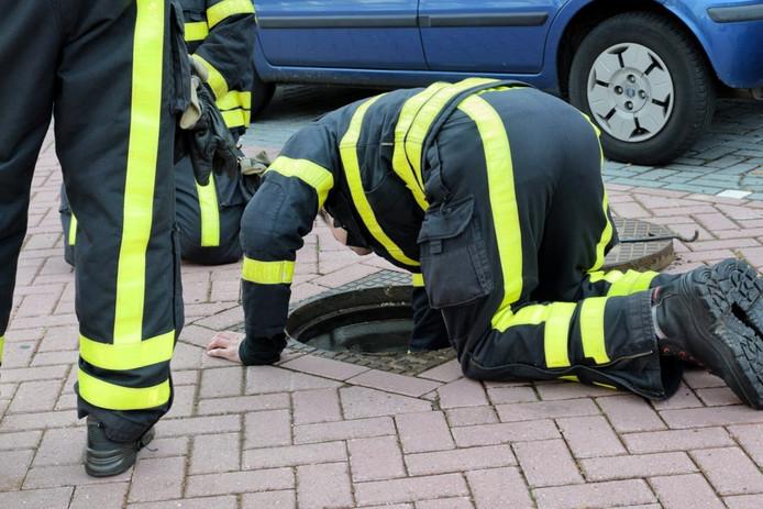 Brandweerlieden doen onderzoek in de rioolputten.