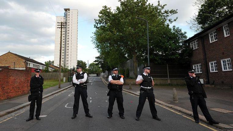 Politieagenten bewaken de straat waar de moord werd gepleegd Beeld afp