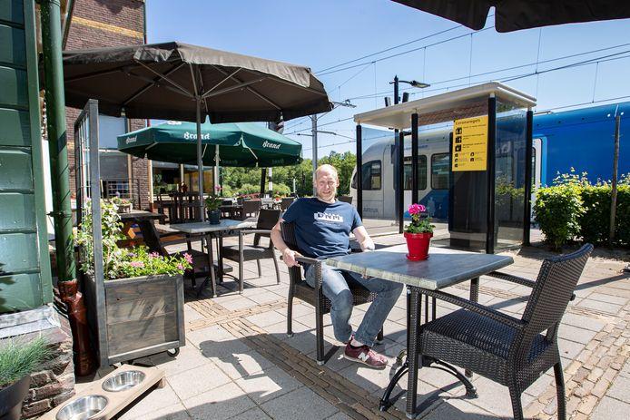 Joost Eilert aan een terrastafel aan de zijkant van Grand Café Het Oude Station. Dankzij de medewerking van NS kan hij ook dit deel gebruiken om zijn terras op anderhalvemeterniveau te krijgen. Ook de gemeente Dalfsen zet het sein op groen.