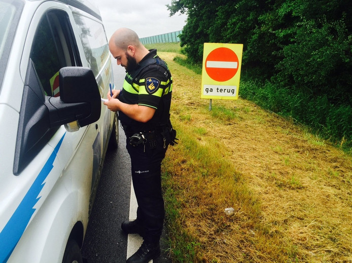 Een politieagent schrijft een bekeuring uit.