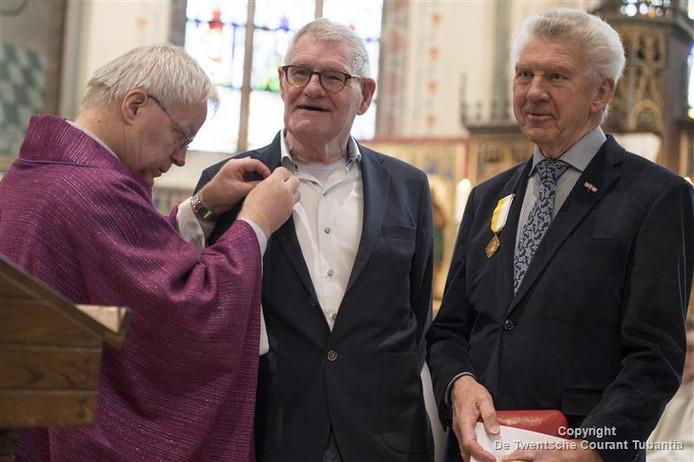 Pastor Munsterhuis speldt Jan Luttikhuis en Frans Swennenhuis de pauselijke onderscheiding op.