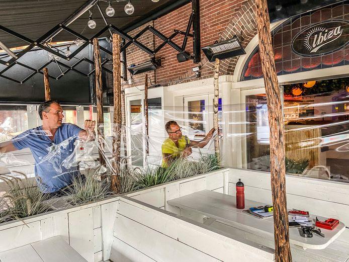 """Michel Vekemans (links), uitbater van Ibiza Tilburg, opende gisteren pas weer zijn zaak. ,,Eerder was het niet rendabel."""" Hier brengt hij 'kuchschermen' op zijn terras aan."""