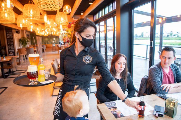Grand Café en Restaurant de Troubadour in Hardenberg, waar personeel sinds deze week al standaard een mondkapje draagt. Susanne Kunst serveert.
