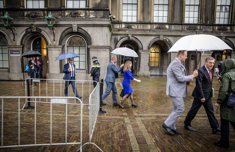 De onderhandelaars van VVD, CDA, D66 en ChristenUnie proberen het droog te houden op het Binnenhof. Beeld ANP