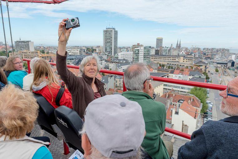 Bezoekers kijken in de Skywatch op 45 meter hoogte uit over de wijk Hazegras en Oostende.