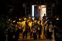 Mannen in witte T-shirts met maskers, helmen en stokken na de aanval op demonstranten bij een metrostation in Yuen Long.