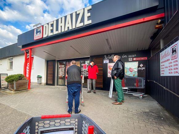 """Een archiefbeeld van enkele weken geleden aan de ingang van een Delhaize in Vlaanderen. Het personeel van de supermarkten is volgens de vakbonden """"moreel en fysiek uitgeput""""."""