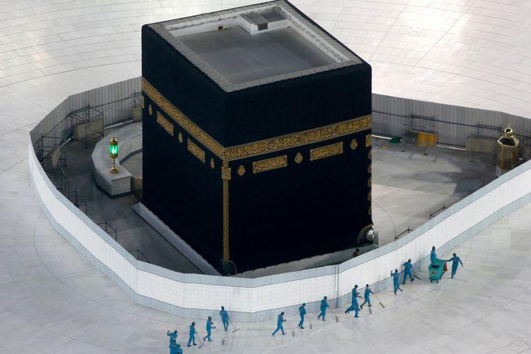 Schoonmakers desinfecteren begin maart het gebied rondom de Kaäba, het heiligdom in Mekka, vanwege het nieuwe coronavirus. Beeld AP