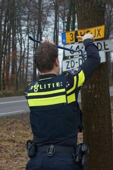 Agenten trekken vastgespijkerde kentekenplaten van boom