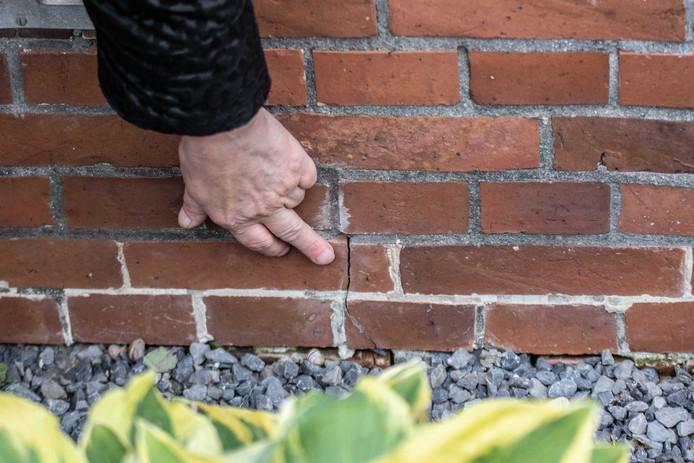 Een bewoonster van Westerwijtwerd wijst schade aan die is ontstaan door een aardbeving.