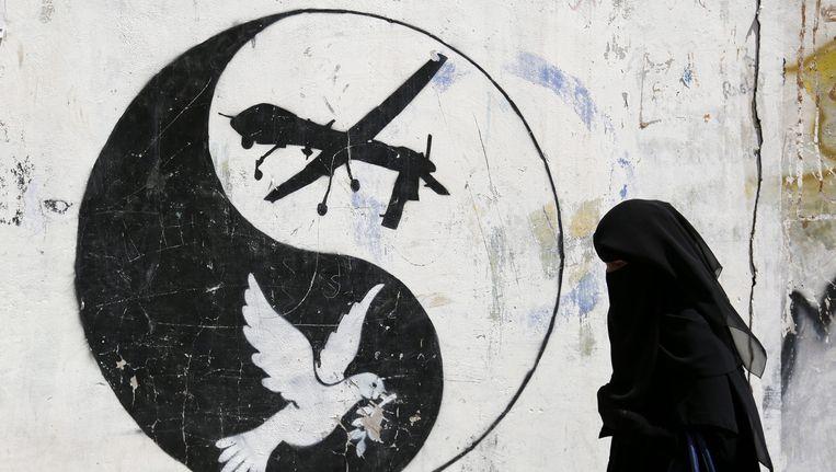 Een Jemenitische vrouw wandelt voorbij graffiti waarin de Amerikaanse droneaanvallen op Jemen worden aangeklaagd.