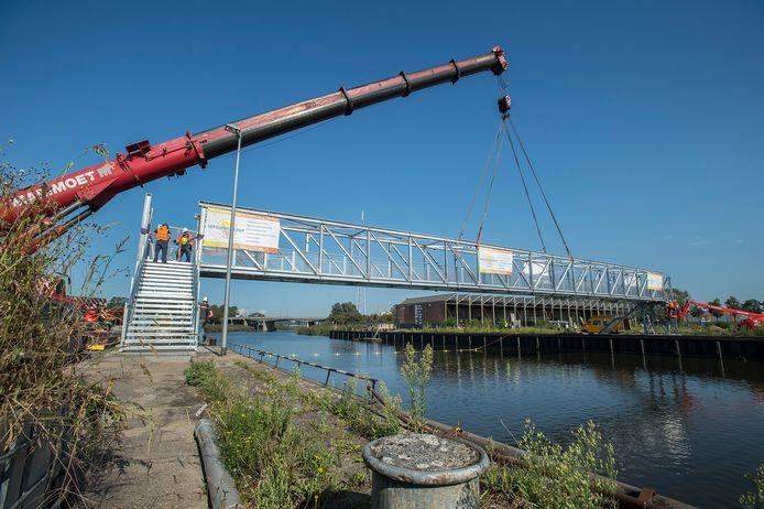 De loopbrug, gebouwd door firma Van Sluisveld uit Heusden, wordt door kranenbedrijf Mammoet over de Belcrumhaven gehangen.