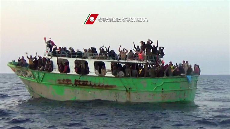 Migranten op een overvol schip op de Middellandse Zee roepen om hulp van een Italiaans kustwachtschip. De still uit een video is vrijgegeven door de Italiaanse autoriteiten. Beeld AFP