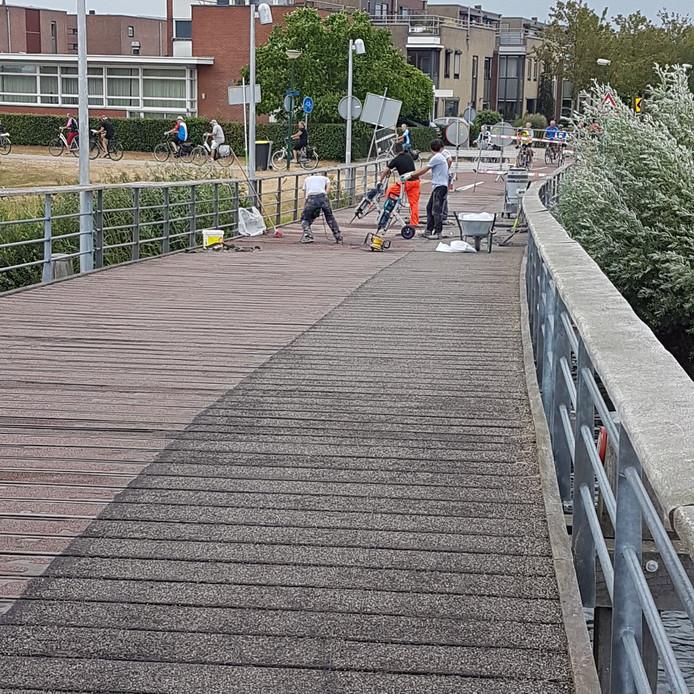 De rode slijtlaag op de Rietplasbrug in Houten krijgt een opknapbeurt.