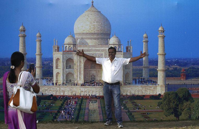 Een vrouw in saree neemt een foto van een man die poseert voor een foto van de Taj Mahal. Beeld epa