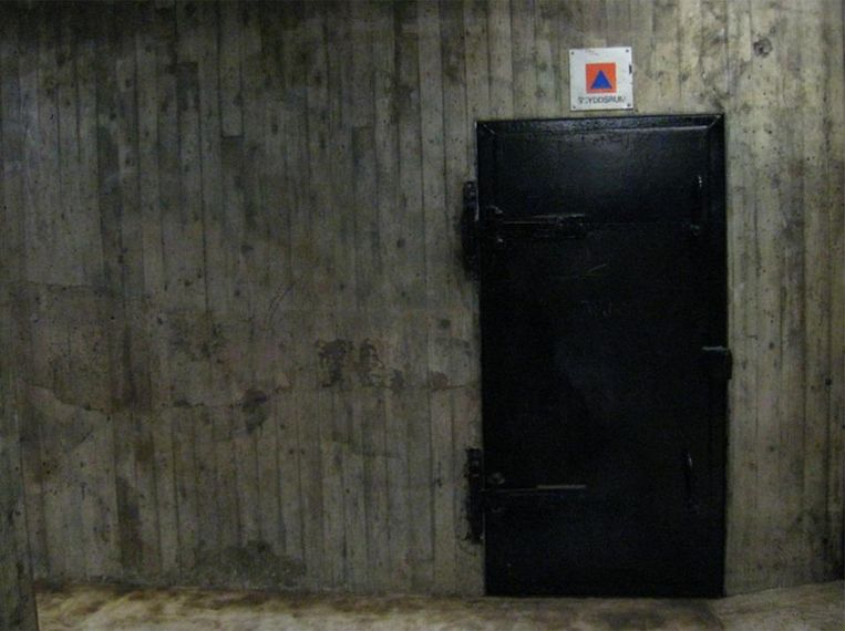 De ingang van een atoomschuilkelder wordt gemarkeerd met een oranje-blauw logo en het woord 'skyddsrum' (schuilplek)