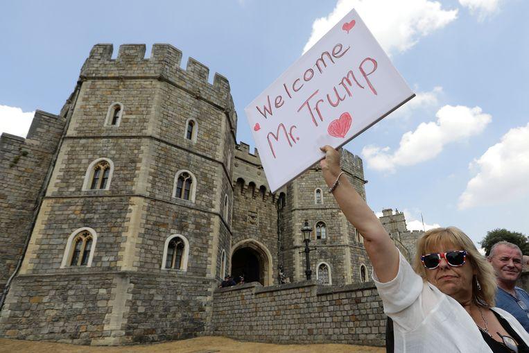 Een Trump-supporter heet de president welkom bij Windsor Castle. Beeld REUTERS