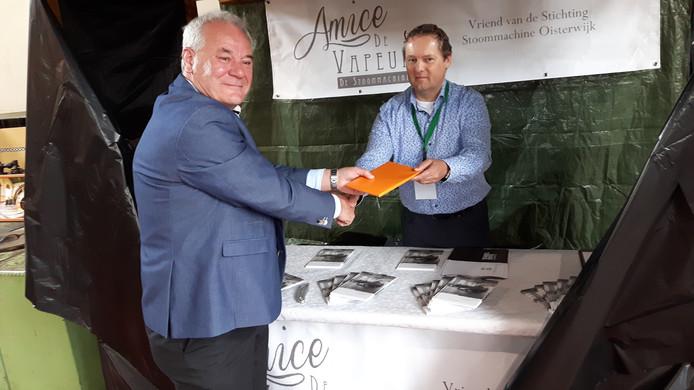 Wethouder Sjef Verhoeven (links) krijgt het eerste exemplaar van het boek over de stoommachine uit handen van Bas de Witte, voorzitter van de Stichting Stoommachine Oisterwijk.
