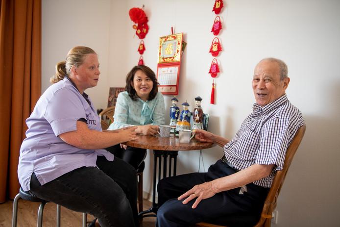 Yingche Su (rechts) is een vrolijke en altijd opgewekte bewoner van Het Weggeler. Hier zit hij aan de koffie met verzorgende Suzanne Beltman en zijn dochter Ajong.