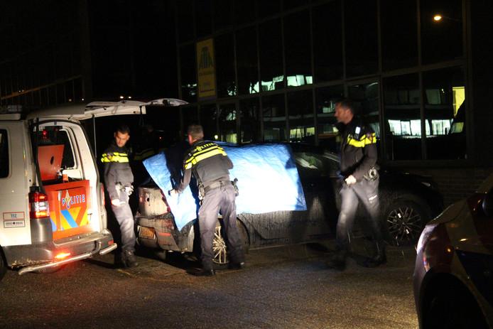 Agenten doen sporenonderzoek bij een geparkeerde auto dicht bij de plek waar het slachtoffer werd aangetroffen.