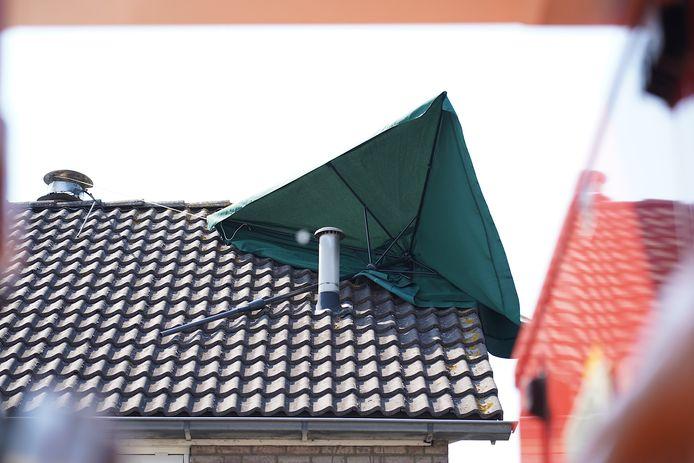 Parasol waait op dak van huis in Dongen, brandweer moet komen met hoogwerker.