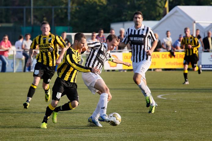 Achilles'29-aanvoerder Tim Verhoeven schermt de bal af voor Theole-aanvaller Jeffrey Heijster.