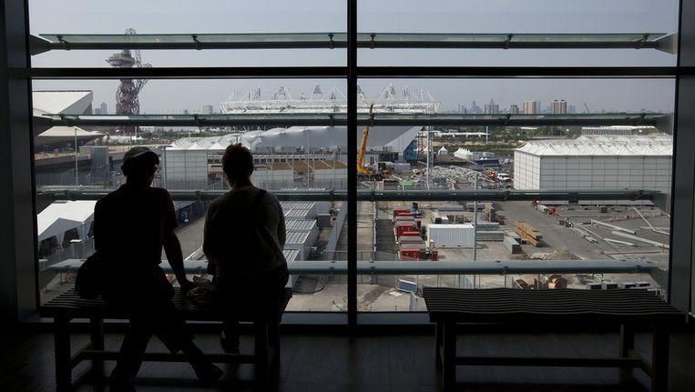 Bezoekers kijken naar de opbouw van het Olympische park in Londen. Beeld null