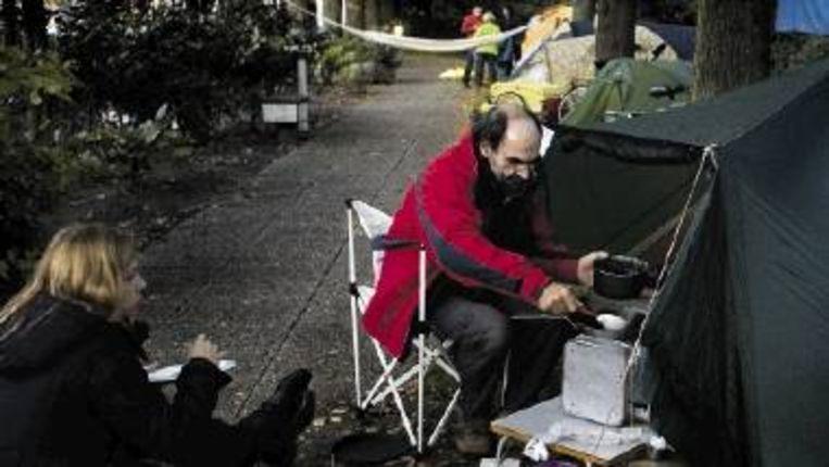 ANWB-medewerker Jan Fraterman bakt een pannekoek. Hij kampeerde vannacht met tientallen collega¿s bij het ANWB-hoofdkantoor in Den Haag. (FOTO JOÿL VAN HOUDT) Beeld